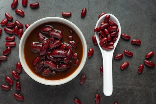 Fagiolo rosso bollito in una ciotola bianca con semi di fagioli rossi in un cucchiaio posto sul pavimento scuro