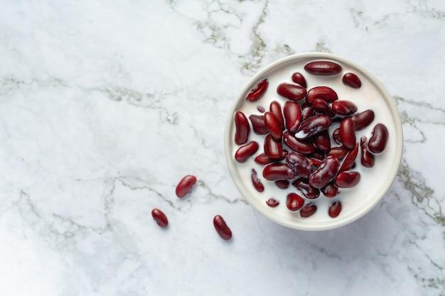 Dessert al latte di cocco di fagioli rossi in una ciotola bianca sul pavimento in marmo bianco