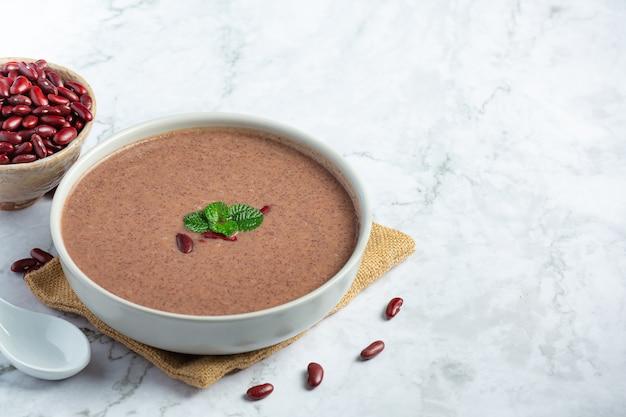 Zuppa calda di fagioli rossi in una ciotola bianca posto sul pavimento di marmo bianco
