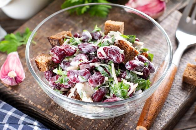 Салат из красной фасоли с гренками на тарелке. здоровое питание, диета