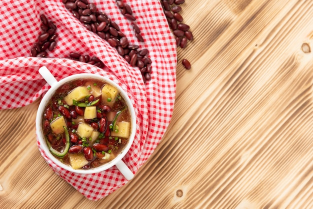 Суп из красной фасоли с картофелем, помидорами и паприкой в керамической посуде. вид сверху.