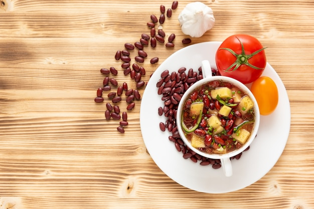 Суп из красной фасоли с картофелем, помидорами и болгарским перцем в керамической посуде. вид сверху.