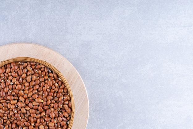 小豆を編みかごに入れ、大理石の表面にある木製の大皿に置きます