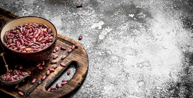 Красная фасоль в миске на старой доске на деревенском фоне