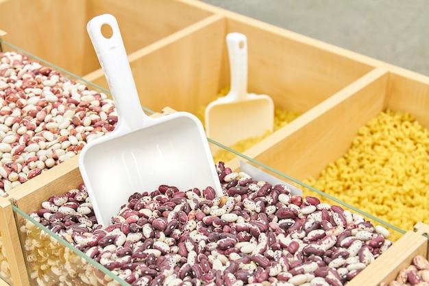Красная фасоль в лотке с пластиковым шпателем зерна в супермаркете