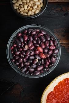 健康的な材料を入れたボウルに小豆を入れ、暗い木製のテーブルに平らに置きます。