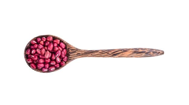 白い背景の上の木のスプーンで小豆