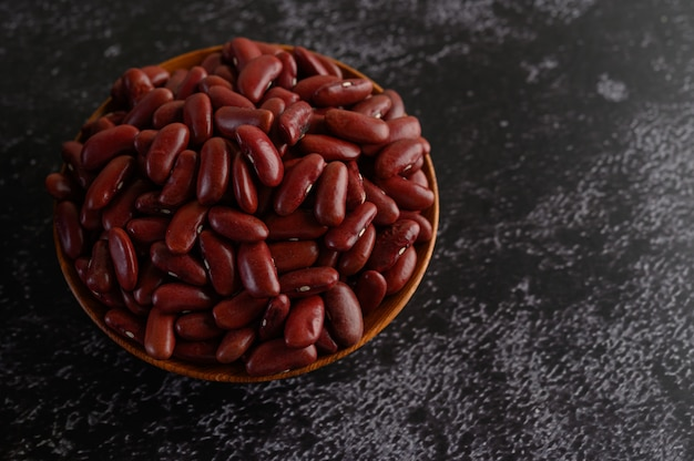 Red beans in a wooden bowl on the black cement floor.