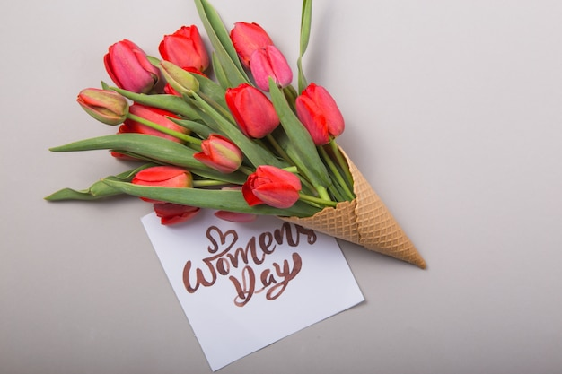 Red  beautiful tulips in an ice cream waffle cone with card womans day on a concrete background. conceptual idea of a flower gift. spring mood