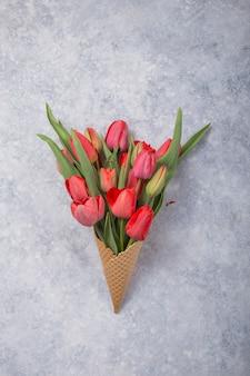 コンクリート背景にアイスクリームワッフルコーンの赤い美しいチューリップ。花の贈り物の概念的なアイデア。春の気分