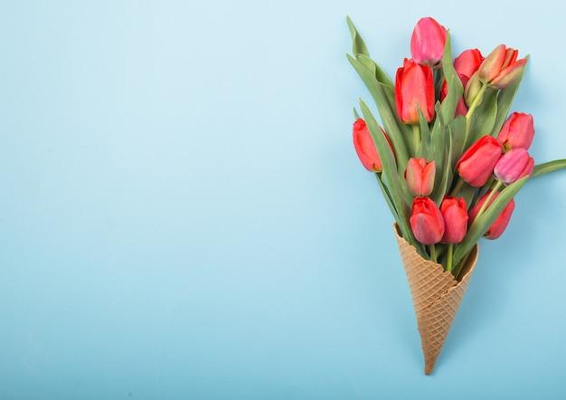 Красные красивые тюльпаны в вафельном конусе мороженого с карточкой женский день на конкретном фоне. концептуальная идея цветочного подарка. весеннее настроение