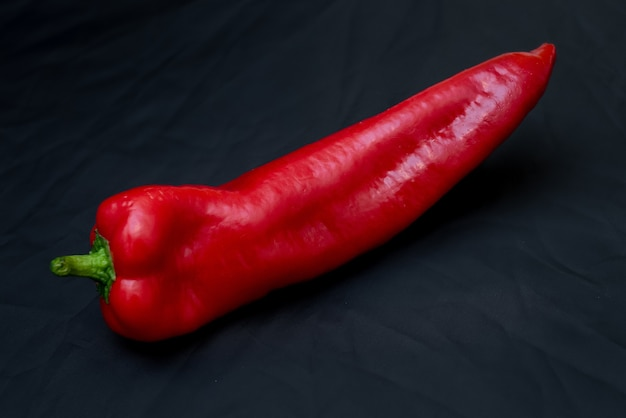 Red bell pepper on black fabric background