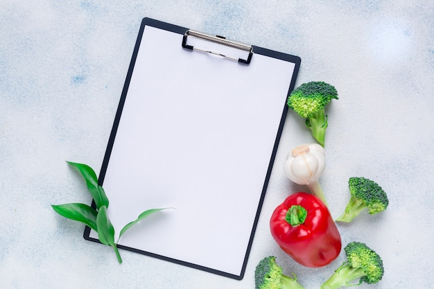 Red bell pepper, broccoli and tablet on a white surface. copy space