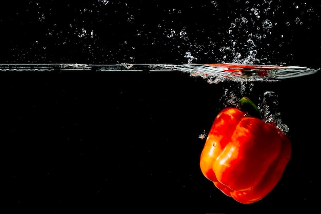 Red bell pepper floating under the clear water