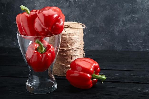 Красный перец в вазе на темном фоне. свежие овощи и концепция продуктов питания. копирование пространства, темный фон, абстракция красного перца.