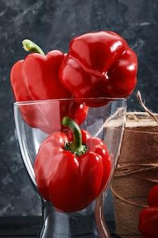 暗い背景の上に花瓶に赤ピーマン