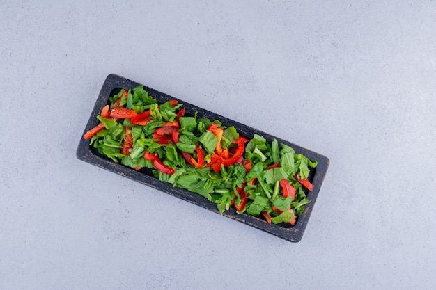 Insalata di peperoni rossi e lattuga in un piccolo vassoio su fondo marmo. foto di alta qualità