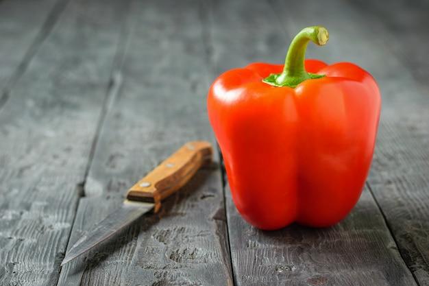 木製のテーブルにナイフで赤ピーマン。ベジタリアンフード。健康的な食事のコンセプトです。