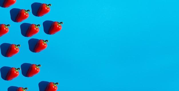 青い背景に濃い黒の深い影のある赤ピーマンが平らに横たわっていた。