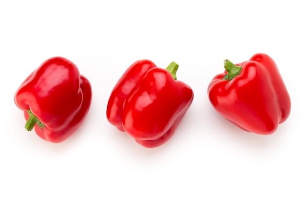 Красный перец с половиной и листьями, изолированные на белом.