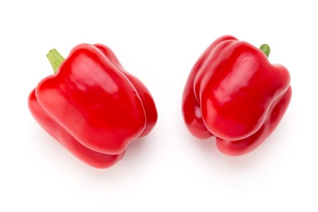 Красный перец с половиной и листьями, изолированные на белом