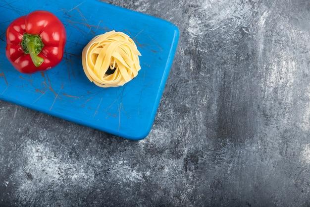 Красный болгарский перец с сырыми макаронными изделиями тальятелле на синей разделочной доске.
