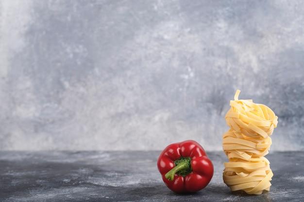 Красный болгарский перец с сырой пастой тальятелле на мраморе.