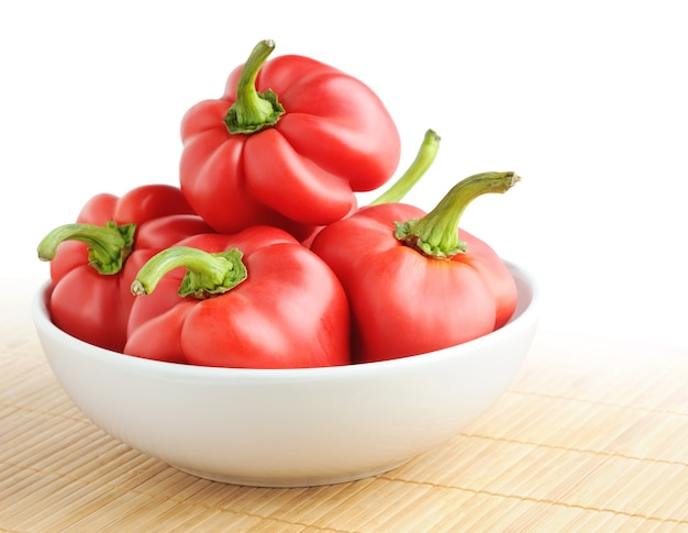 Red bell peppers in a bowl on bamboo mat isolated on white space