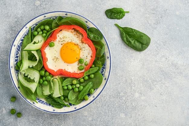밝은 회색 테이블 배경에 있는 아침 접시에 달걀, 시금치 잎, 완두콩, 마이크로그린으로 채워진 빨간 피망. 평면도.