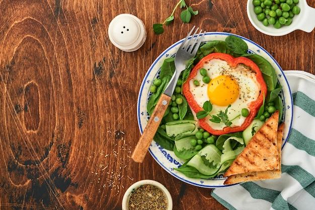 오래된 나무 테이블 배경에 있는 아침 접시에 달걀, 시금치 잎, 완두콩, 마이크로그린으로 채워진 빨간 피망. 평면도.