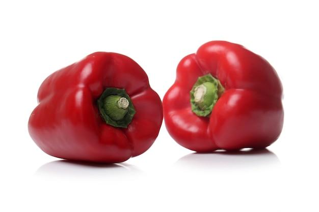 Peperoni dolci rossi su una superficie bianca