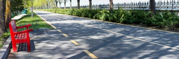 Красная скамейка у аллеи в парке. асфальтированная дорога для велосипедистов и прогулок по парку.