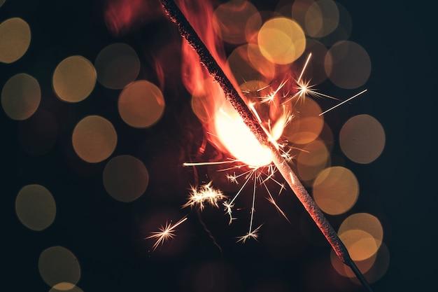 Red bengal sparkle lights close up on dark background