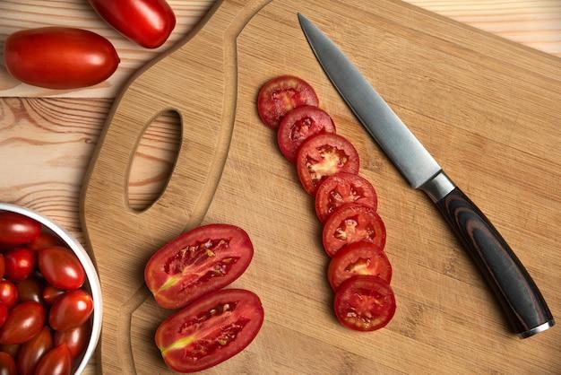 Красные ягоды и нарезанные помидоры на деревянном столе