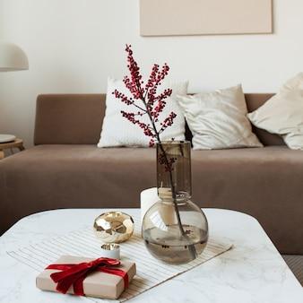 꽃병에 붉은 열매, 커피 테이블에 종이 선물 상자. 편안한 현대적인 인테리어 디자인 컨셉