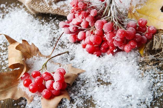 Красные ягоды калины и снега на вретище, на деревянном фоне