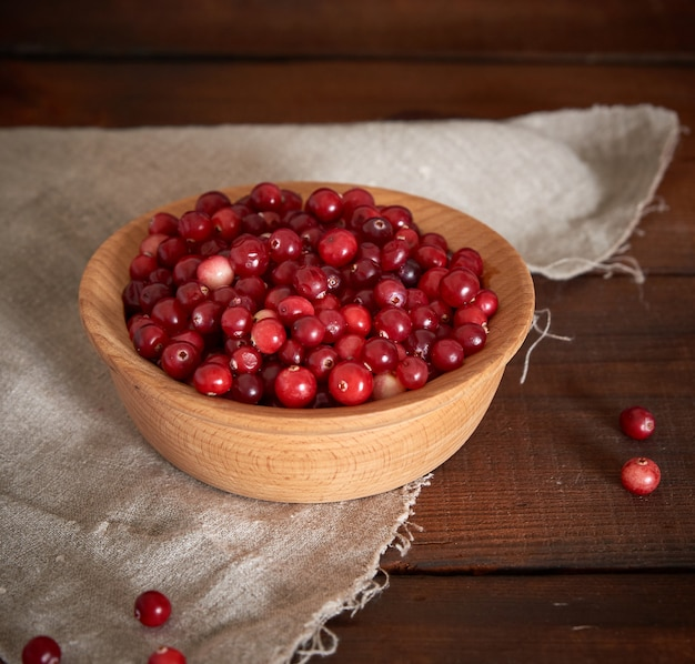 Red berries of ripe lingonberries in a wooden bowl
