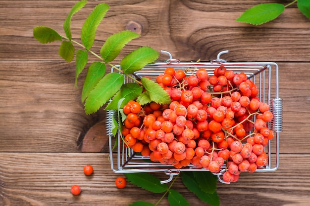 Red berries and rowan leaves in a metal basket on woodtable top view