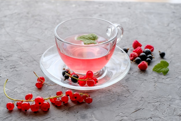 Red berries tea in cup and teapot