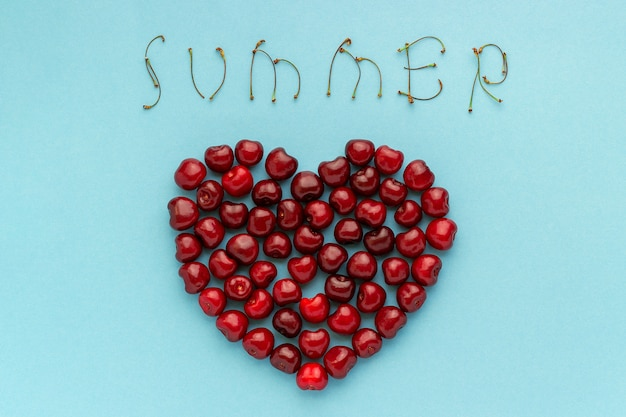 Red berry cherries in shape of heart and text summer