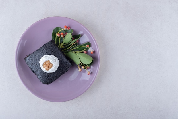 Bacca rossa con torta di brownies con noce sulla piastra, sul marmo.