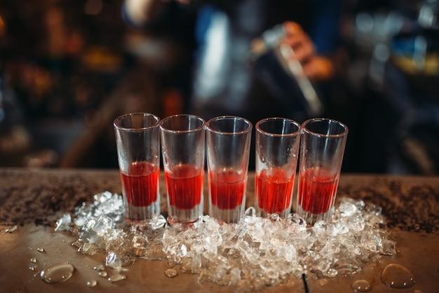 グラスに赤い飲み物とバーカウンターの氷
