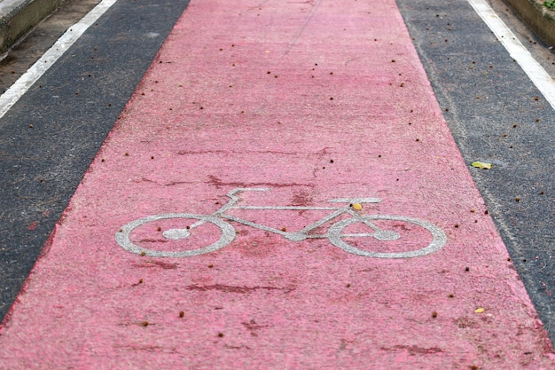 Red bicycle lane on the street with white bicycle icon.