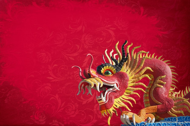 Red big dragon statue on red texture background .