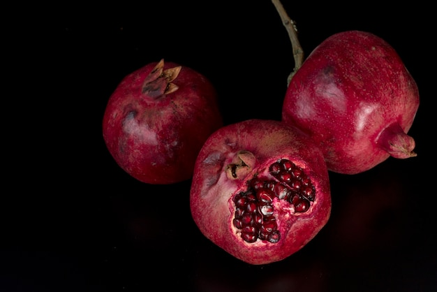 Red big pomegranates on black, top view