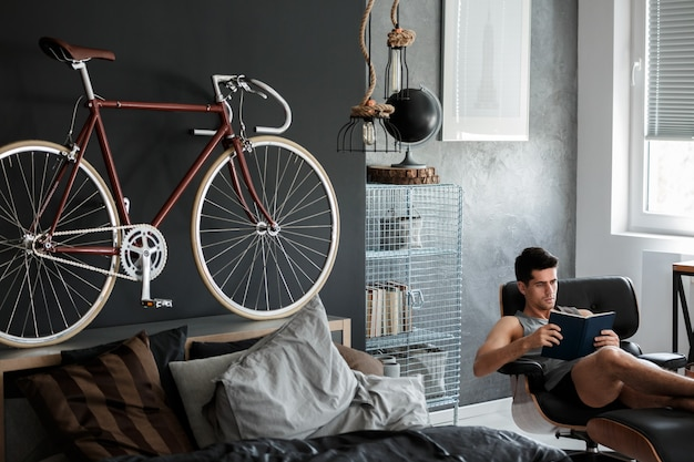 Red bike on wooden bolster of king-size bed in mannish room with black globe on metal shelf