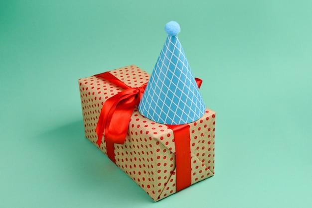 赤い誕生日キャップと緑の背景にプレゼント。テキストまたはデザインのためのスペース。