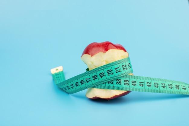 コピースペースのある青い表面に赤いかまれたリンゴと巻尺