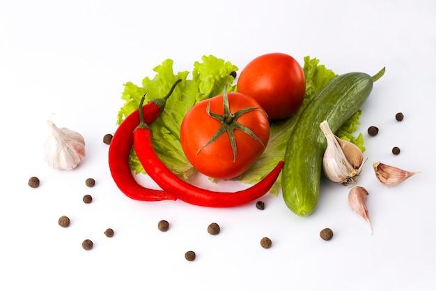 白い背景に赤ビターペッパーキュウリとトマト。アベル背景に新鮮な野菜。