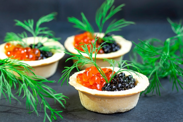 Red and black caviar lie in sand baskets